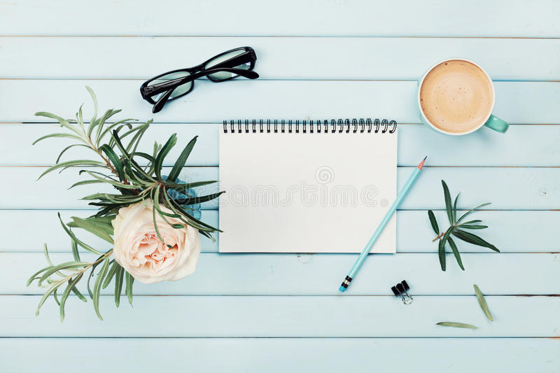 Morning coffee cup, clean notebook, pencil, eyeglasses and vintage rose flower in vase on blue rustic desk overhead view. stock photos