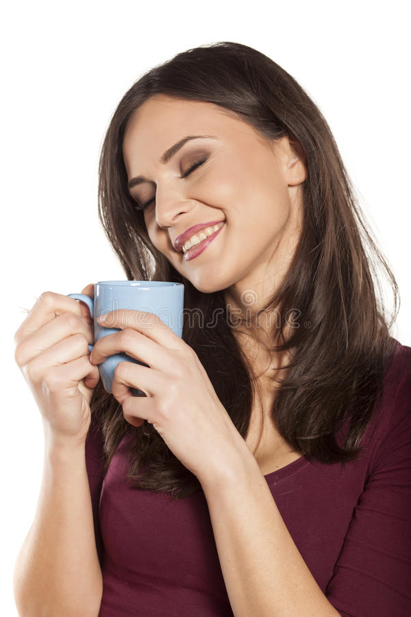 Morning coffee. Happy young woman enjoying the smell of morning coffee royalty free stock images