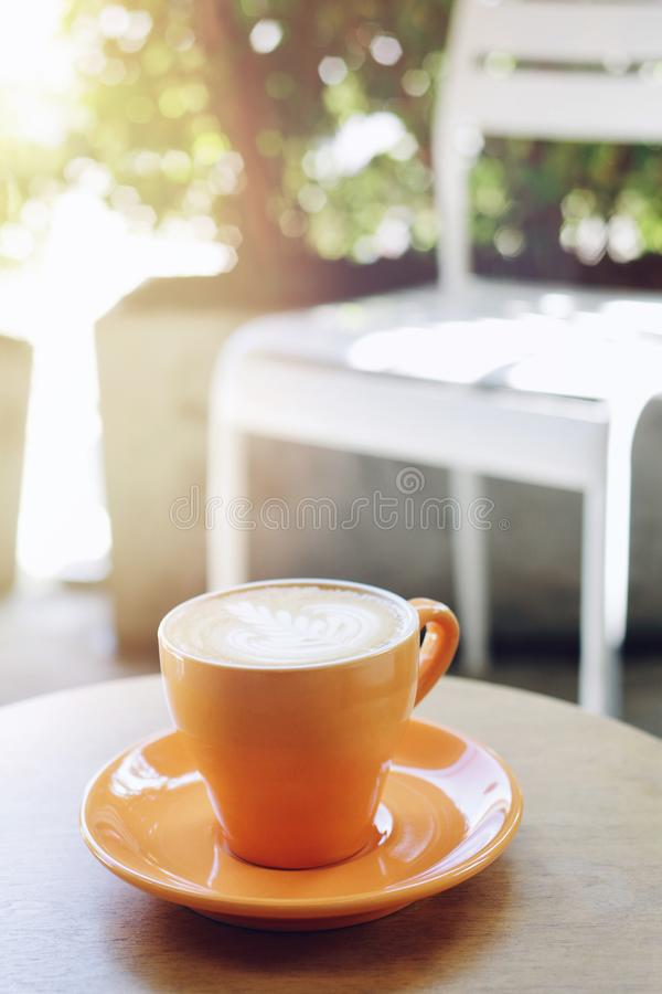 Morning coffee hot latte in orange cup with saucer on wood table coffee shop garden blurred background.  royalty free stock images