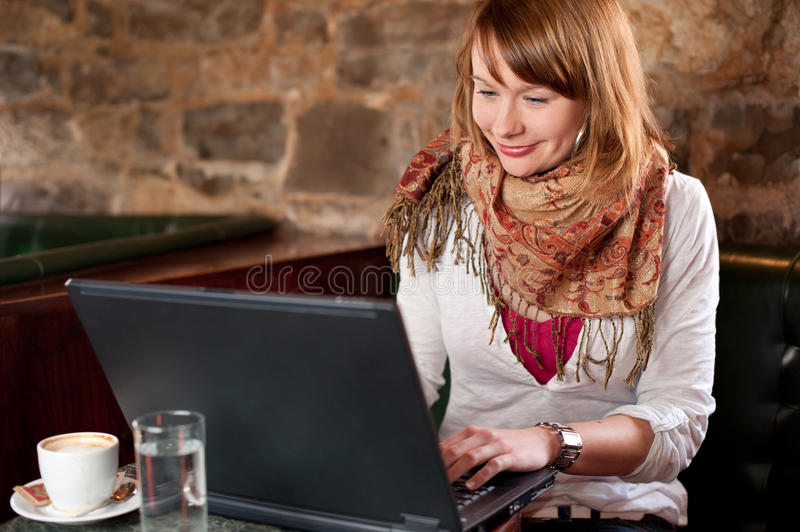 Morning coffee in internet cafe. Beautiful young girl checking news on web and drinking coffe stock image