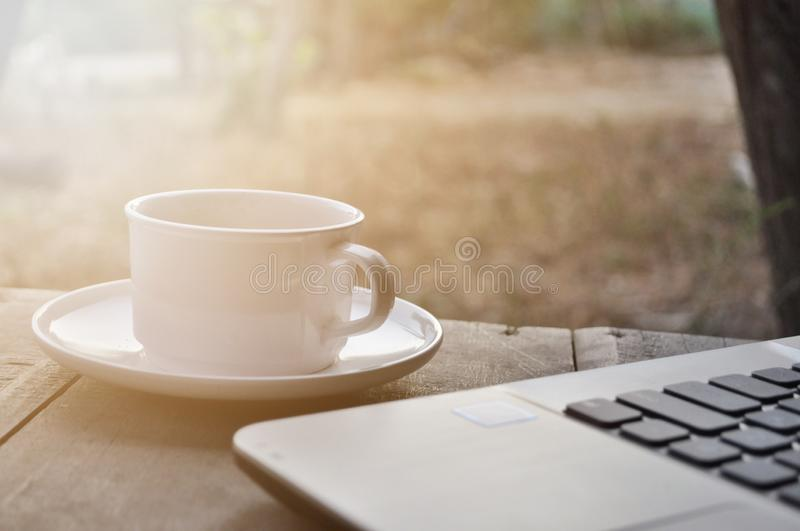 Morning coffee with laptop. Morning coffee and laptop on wooden table royalty free stock photos