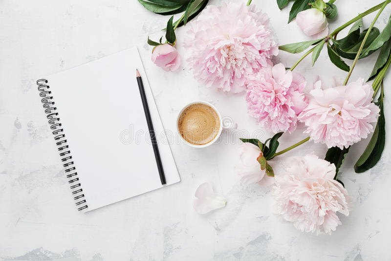 Morning coffee mug for breakfast, empty notebook, pencil and pink peony flowers on white stone table top view in flat lay style. Woman working desk