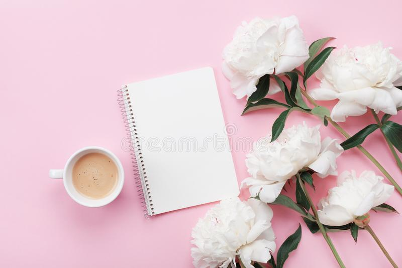 Morning coffee mug for breakfast, empty notebook and white peony flowers on pink pastel table top view in flat lay style. stock photo