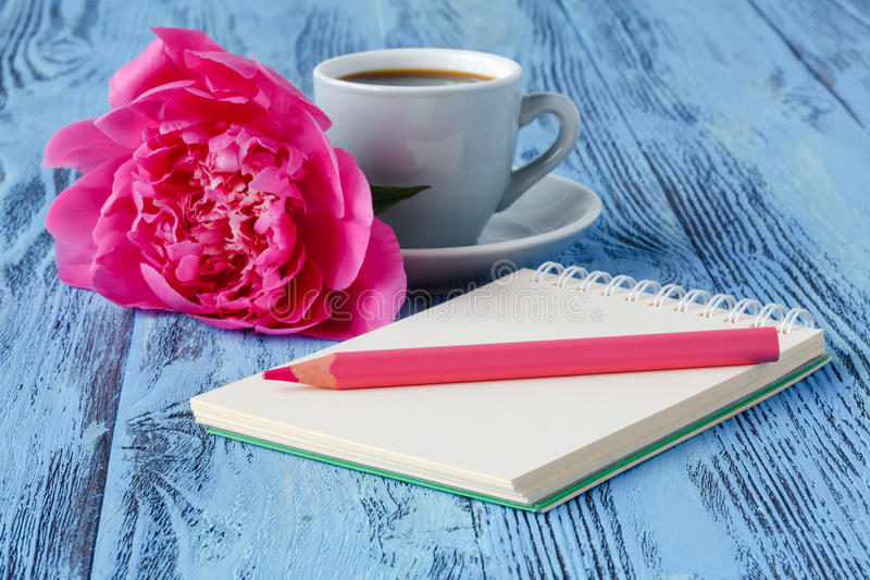 Morning coffee mug, empty notebook, pencil and white peony flowers on blue wooden table royalty free stock images