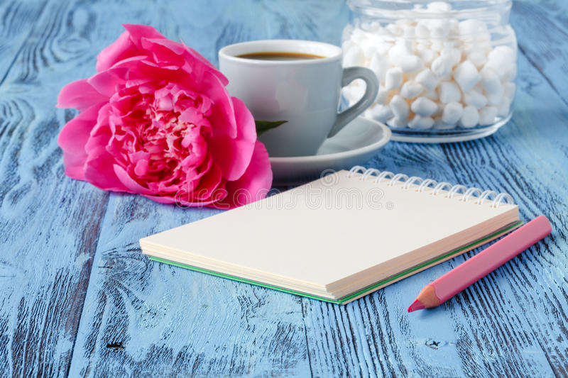 Morning coffee mug, empty notebook, pencil and white peony flowers on blue wooden table stock images