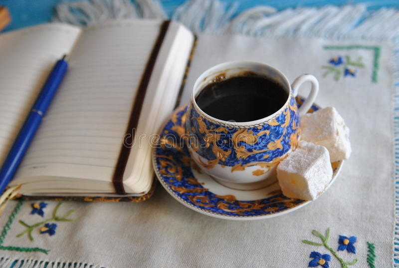 Morning coffee: porcelain cup with coffee and turkish delight and notebook royalty free stock photo