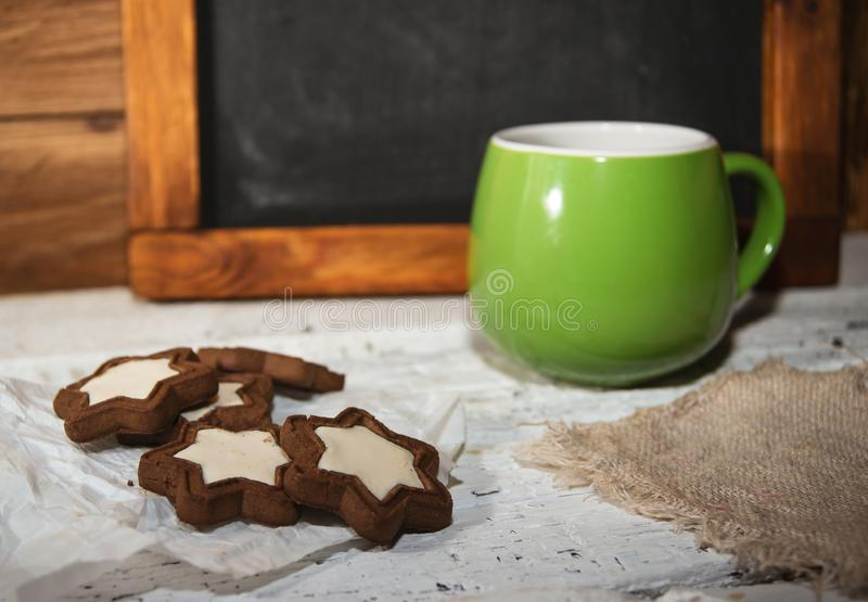 Morning coffee with some star-shaped chocolate cookies. On wooden background royalty free stock photos