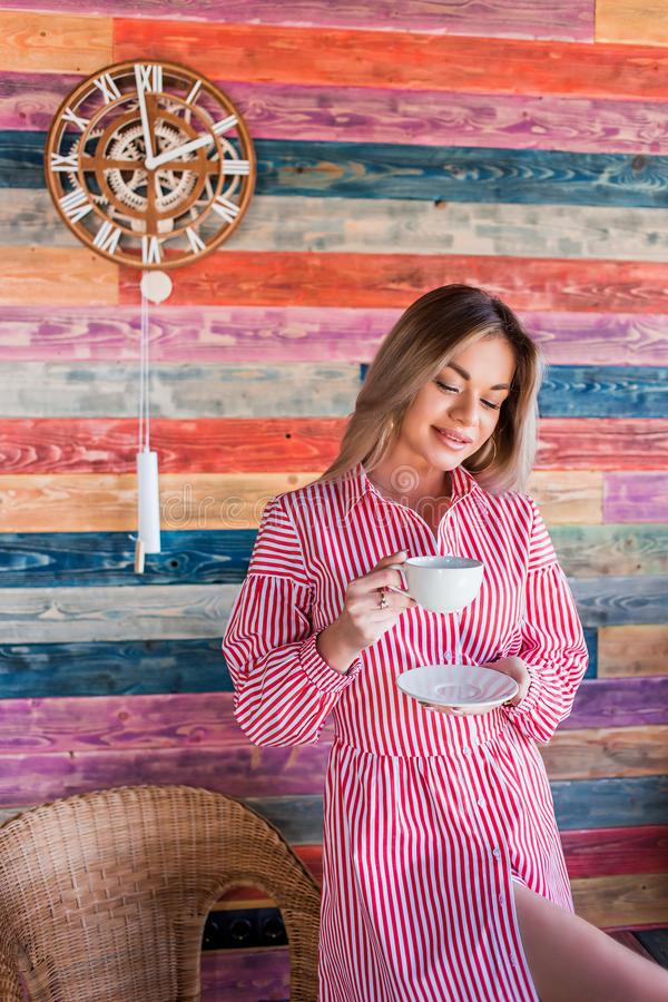 Morning coffee and tea. Beautiful attractive woman sitting and holding a white Cup royalty free stock photos