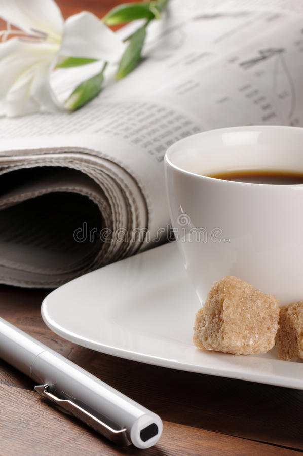 Morning coffee time with newspaper. And flower on the background stock image