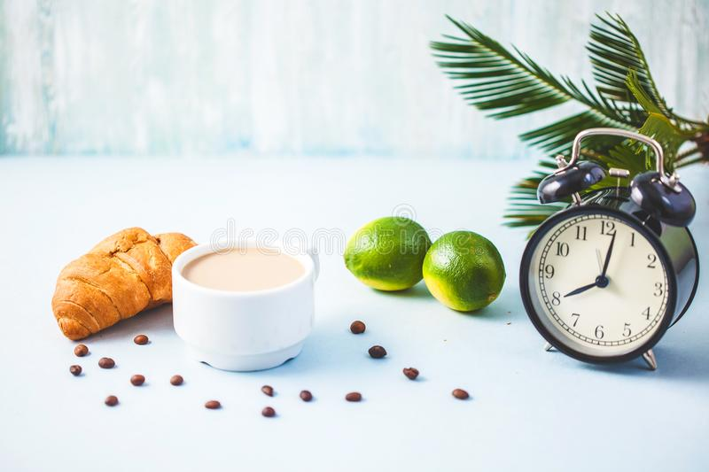 Morning coffee in a white cup Croissant Lime on a light background Wake-up with an alarm clock Breakfast cheerfulness, a healthy b stock photography