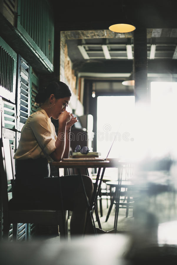Morning coffee and work. Asian business woman drinking coffee and working on laptop in restaurant stock images
