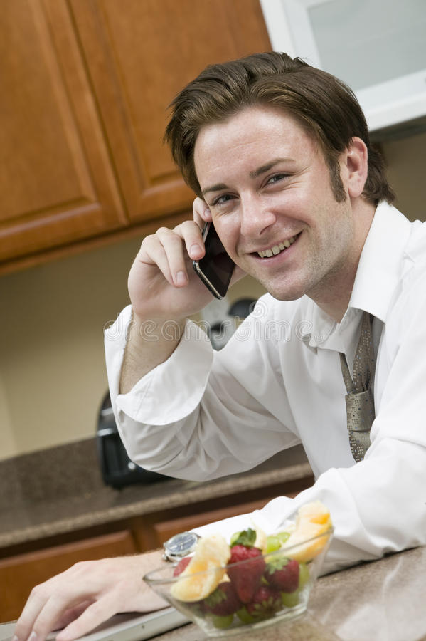 Morning Conference Call. A young businessman talking on his phone while eating his morning breakfast stock images
