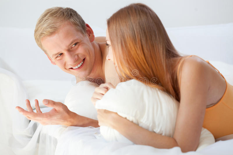 Morning conversation in bed. Horizontal view of morning conversation in bed royalty free stock image
