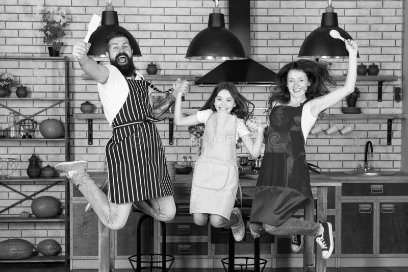 Morning cooking. Family day. Father, mother and child chef cooking. Mother and father with little girl. Happy family in. Kitchen. Little girl with parents in royalty free stock image