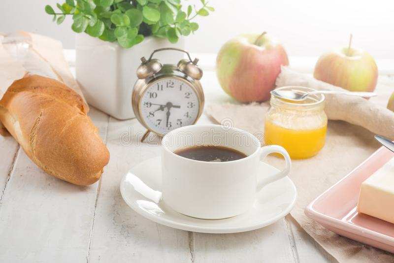 Morning cup of coffee, alarm clock, apples, butter and baguette, in a light kitchen. Background area, the concept of a bright morn. Ing and breakfast royalty free stock photo