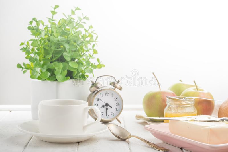 Morning cup of coffee, alarm clock, apples, butter and baguette, in a light kitchen. Background area, the concept of a bright morn. Ing and breakfast stock photography