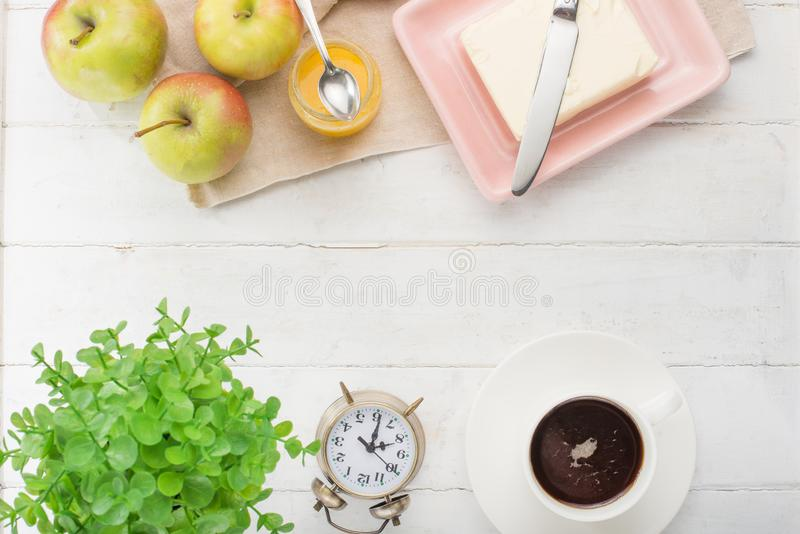 Morning cup of coffee, alarm clock, apples, butter and baguette, in a light kitchen. Background area, the concept of a bright morn. Ing and breakfast. Top view royalty free stock images