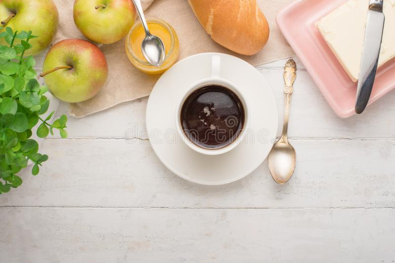 Morning cup of coffee, alarm clock, apples, butter and baguette, in a light kitchen. Background area, the concept of a bright morn. Ing and breakfast. Top view royalty free stock image