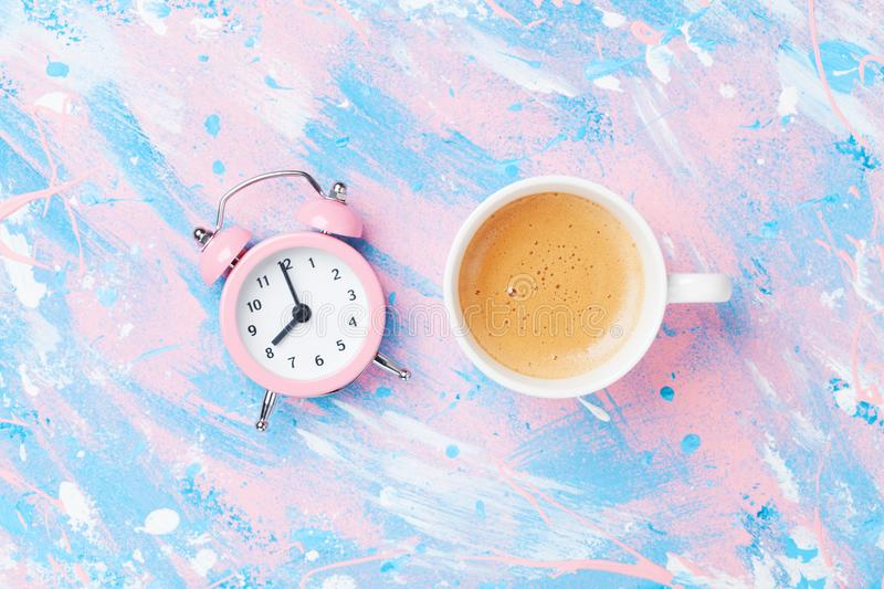Morning cup of coffee and alarm clock on colorful working desk top view in flat lay style. Punchy pastel background. royalty free stock image