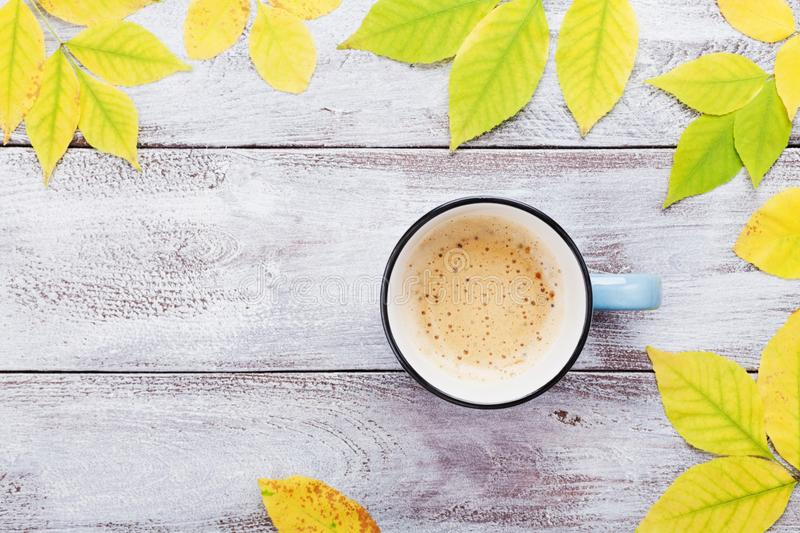 Morning cup of coffee and autumn leaves on vintage wooden table top view. Cozy breakfast. Flat lay style. stock images
