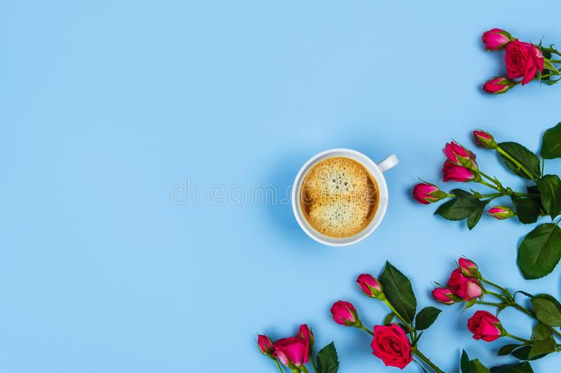 Morning Cup of coffee and a beautiful roses on blue background, top view. Blue background with a Cup of coffee surrounded by flowers. Flat lay, top view royalty free stock photos