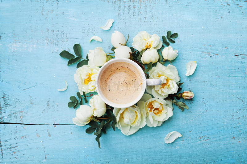 Morning cup of coffee and beautiful roses flowers on turquoise rustic table top view. Cozy Breakfast. Flat lay style. Morning cup of coffee and beautiful roses stock image