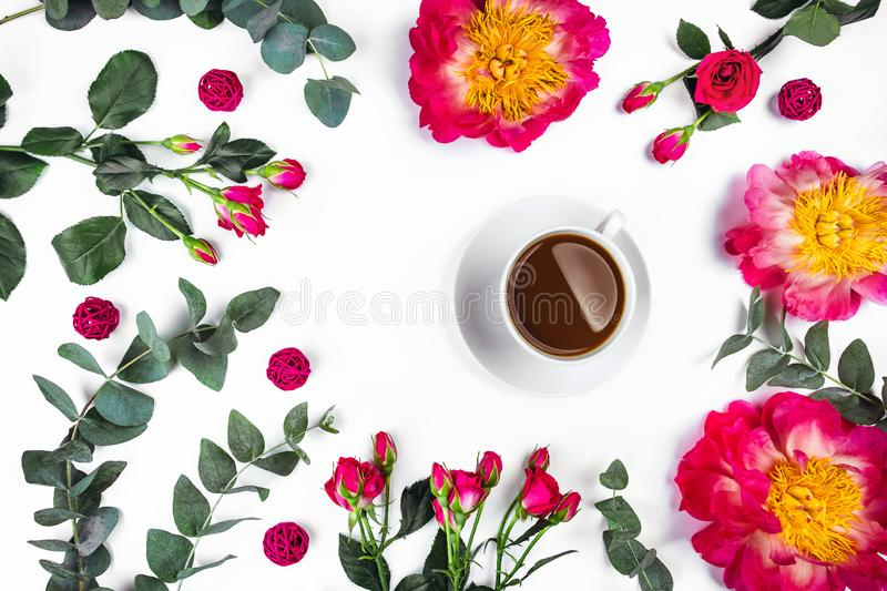 Morning Cup of coffee and a beautiful roses and peonies on white background, top view. Isolated white background with a Cup of coffee surrounded by flowers stock photography