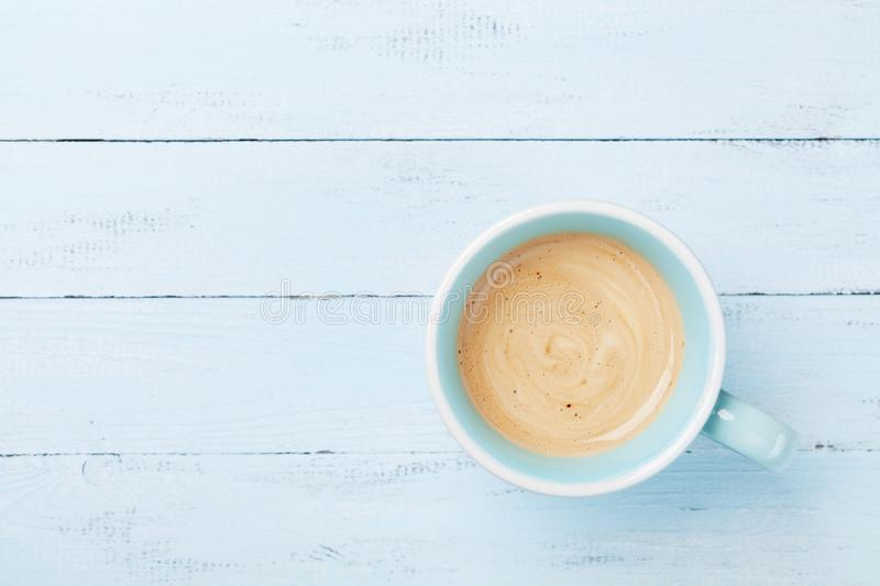 Morning cup of coffee on blue wooden table top view. Morning cup of coffee on blue wooden table from above stock photos
