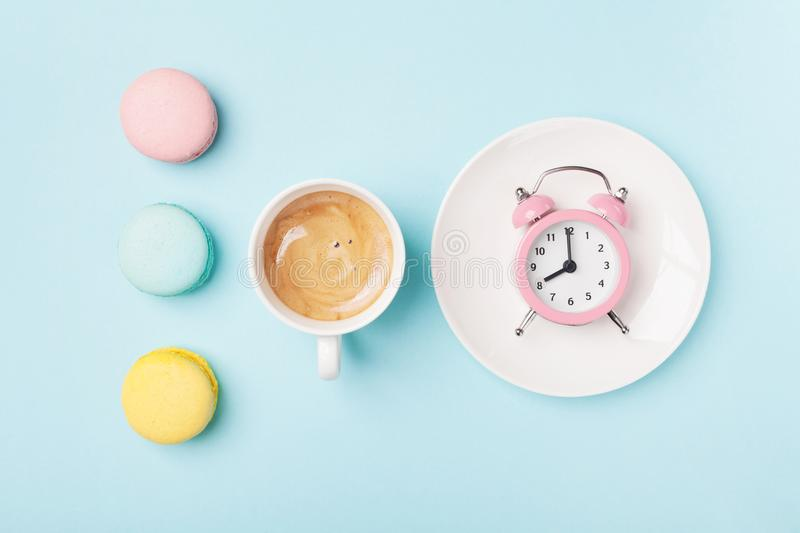 Morning cup of coffee, cake macaron and alarm clock on light turquoise table top view. Flat lay style. Beautiful breakfast. Sweet macaroons royalty free stock photography