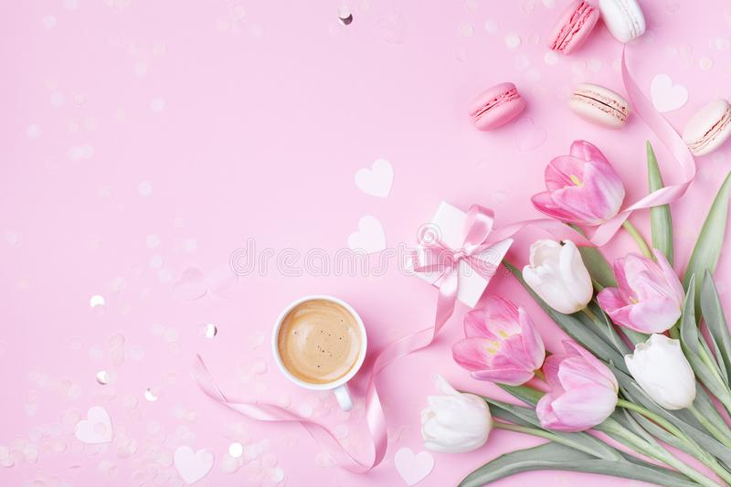 Morning cup of coffee, cake macaron, gift box and spring tulip flowers on pink background. Beautiful breakfast for Women day. Mother day. Flat lay royalty free stock photo