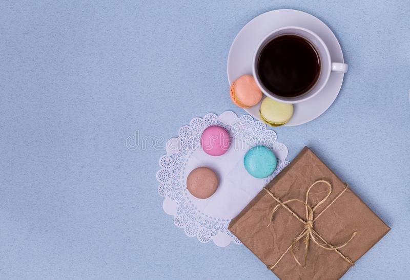 Morning cup of coffee, cake macaron, gift or present box on blue table from above. Beautiful breakfast. Flat lay style stock images