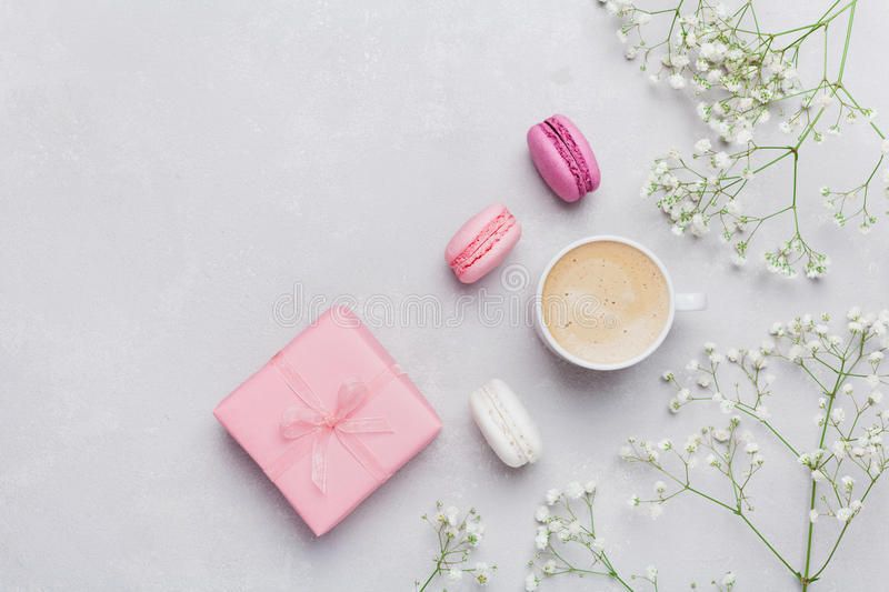 Morning cup of coffee, cake macaron, gift or present box and flower on light table from above. Beautiful breakfast. Flat lay. royalty free stock photography