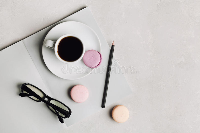 Morning cup of coffee, empty notebook, pencil, glasses and cake macaron on gray desk overhead view. Beautiful breakfast. Flat. Morning cup of coffee, empty stock image
