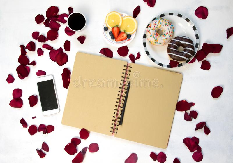 Morning Cup of coffee, empty notebook and roses flowers, fruits and donuts on white table from above. Cozy Breakfast royalty free stock image