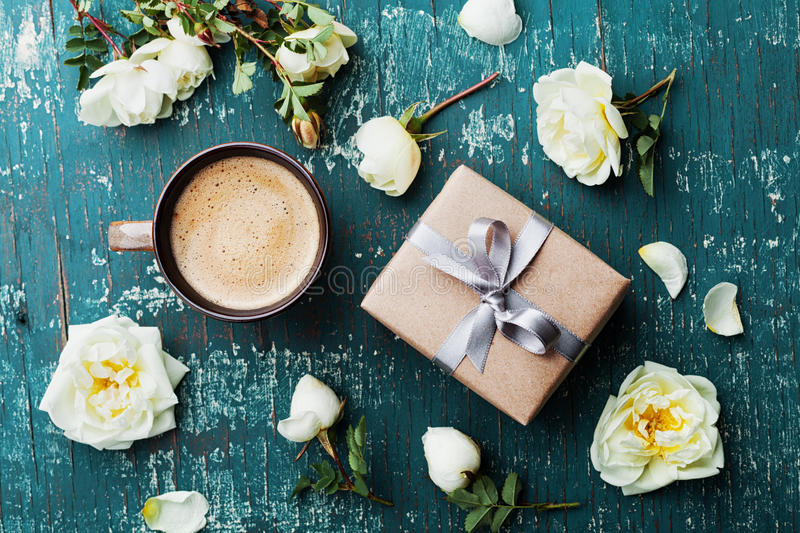 Morning cup of coffee, gift box and beautiful roses flowers on teal vintage table top view. Cozy Breakfast. Flat lay style. royalty free stock photo