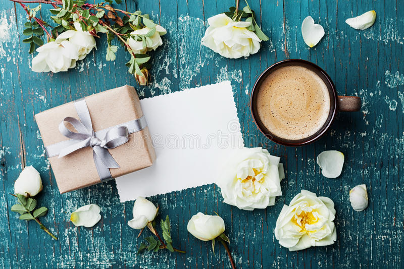 Morning cup of coffee, gift box, notes and beautiful roses flowers on teal vintage background top view. Cozy Breakfast. Flat lay. royalty free stock photography