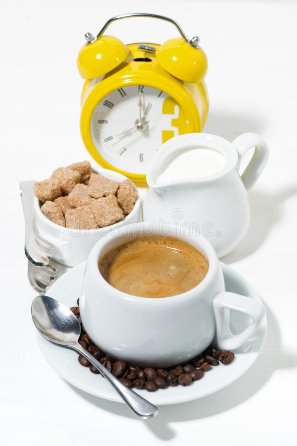 Morning cup of espresso and alarm clock on white background. Vertical, closeup stock photos