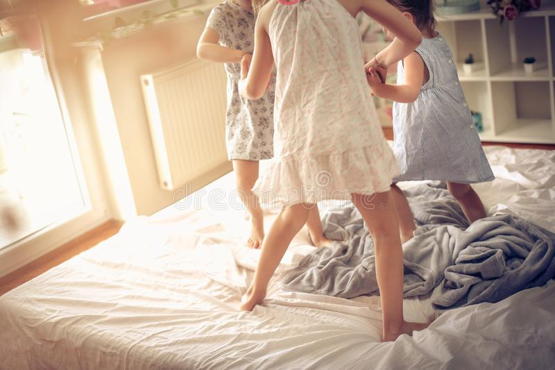 Morning dance. Kids on bed. Three little girls dancing in bed. Space for copy stock images