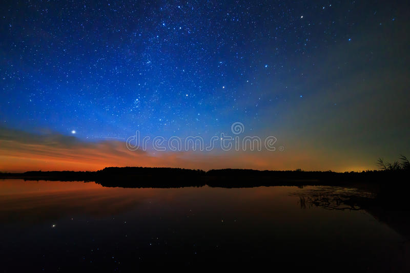 Morning dawn on starry background sky reflected in the water stock photo