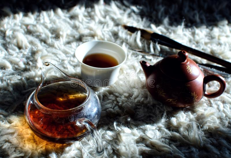 Chinese tea puer, cup and teapot with shadows in sunny day stock images