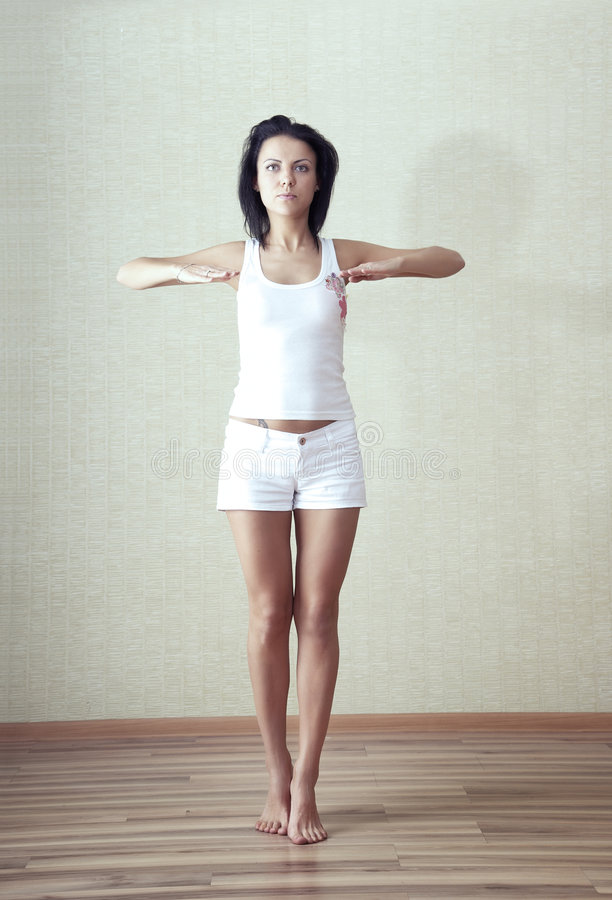 Morning exercise. Lady in casual clothing doing morning exercise at home stock photo