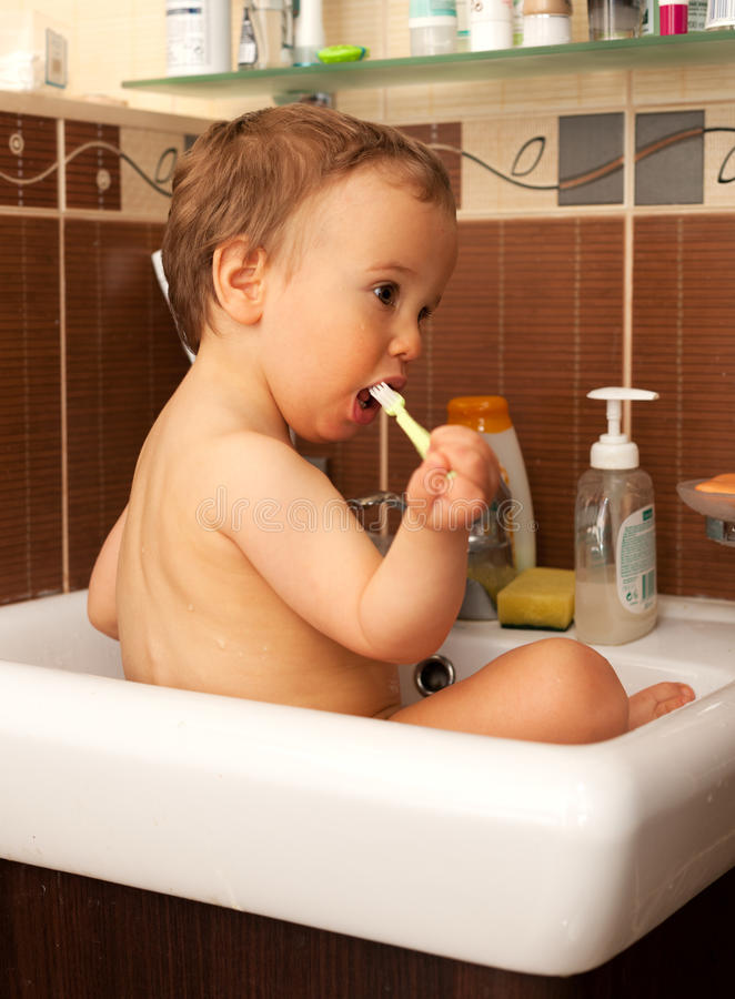 Morning exercises. Baby sitting in sink and brusing teeth stock photos