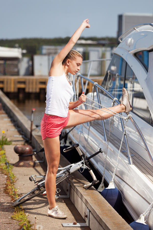 Morning exercises. Girl stretching after the morning bicycle run royalty free stock image