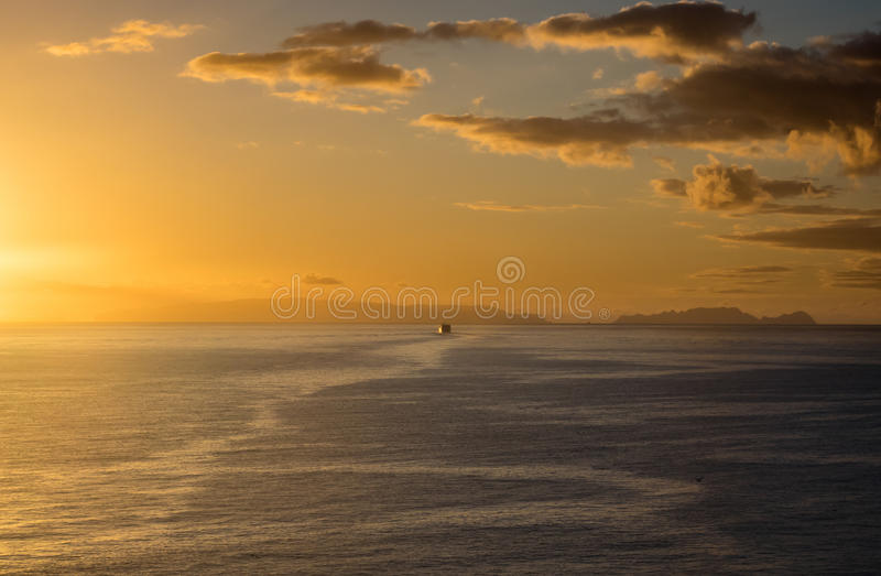 Morning ferry sailing away to distant islands in the morning glow of the sunrise stock photography