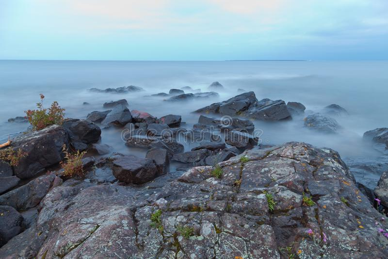 Morning fog covered rocky shore of Lake Superior. Overcast sky and calm water of the Lake Superior stock photos
