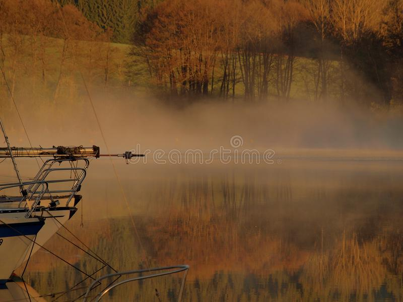 Morning fog on the Lipno lake. Spring, water and boat, romantic. calm surface stock image