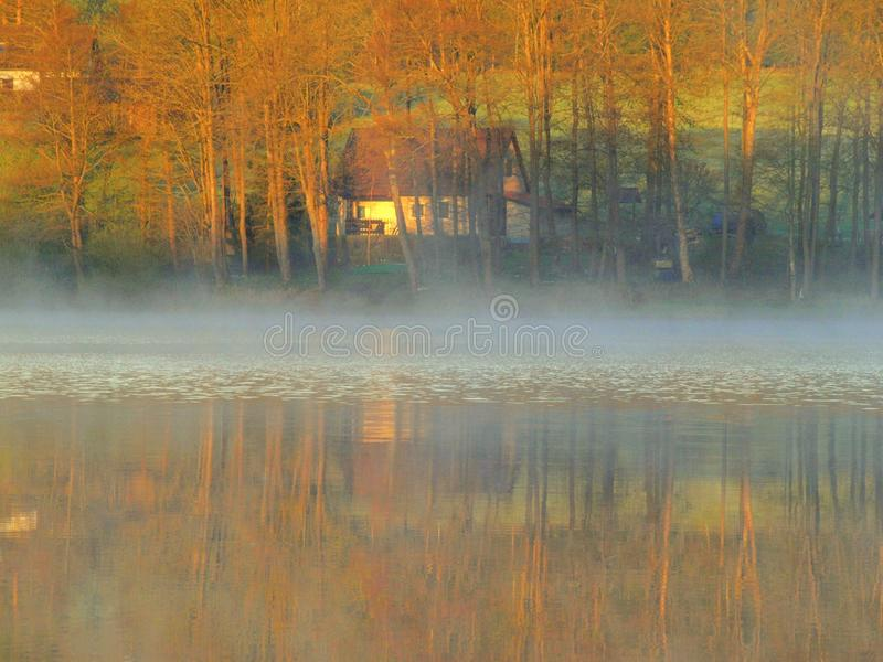 Morning fog on the Lipno lake. Spring, water and boat, romantic. calm surface, house in the background royalty free stock photos