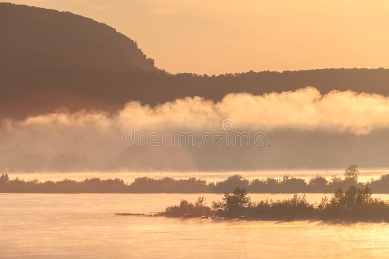 Morning fog rises over the river in the light of the rising sun against the silhouettes of mountains and Islands royalty free stock photos