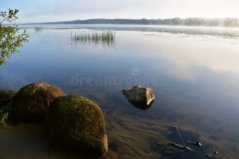 Morning fog on the river, in the water large stones moss lichen, sandy bottom royalty free stock photos
