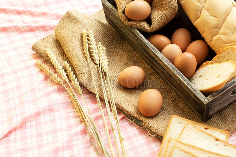 Morning food. breakfast and baked bread concept. Fresh fragrant bread and egg on the fabric sack. On wooden table stock images